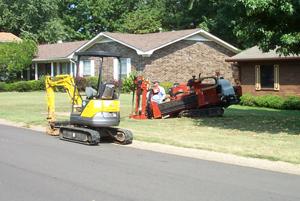 Workers in machines dig into the ground to investigate a residential water leak.