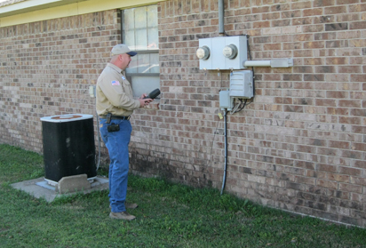 A man reads the meter outside of a brick building